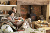 Young couple relaxing by fire — Stock Photo