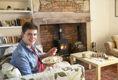 Young man eating meal by fire — Stock Photo