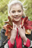 Young woman with autumn leaves — Photo