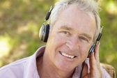 Homem sênior com fone de ouvido — Foto Stock