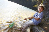 Happy boy fishing at lake — Stock Photo
