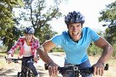 Jeune couple en balade à vélo pays — Photo