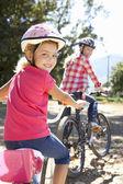 Liten flicka på land cykel rida med mamma — Stockfoto
