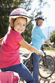 Little girl on country bike ride with grandma — Stock Photo