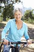 Senior woman on country bike ride — Stok fotoğraf