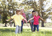 Parents playing with children in country — Stock Photo