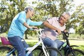 Senior couple playing on children's bikes — Stock Photo
