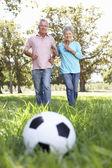 Senior couple playing football — Stock Photo