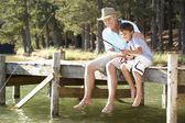 Senior man fishing with grandson — Stock Photo
