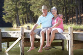 Senior couple sitting by lake — Stock Photo