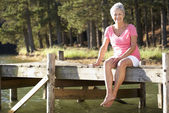 Senior woman sitting by lake — Stock Photo