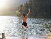 Niño saltando en lago — Foto de Stock