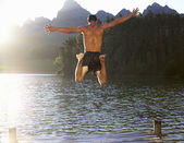 Young man jumping into lake — Stock Photo