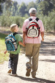 Senior man and grandson on country walk — Stock Photo