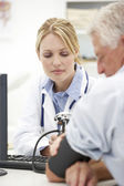 Young doctor with senior patient — Stock Photo