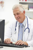 Senior doctor at desk — Stock Photo