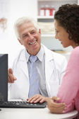 Senior doctor with female patient — Stock Photo