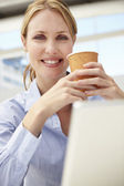 Businesswoman with laptop and coffee — Stock Photo