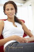 Mujer joven sentada en la silla — Foto de Stock