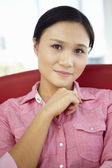 Young woman sitting in chair — Stockfoto