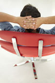Young man relaxing in red chair — Foto de Stock