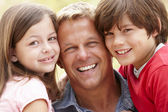 Portrait father and children outdoors — Stock Photo