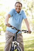 Senior Hispanic man riding bike — Stock Photo