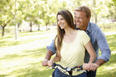 Couple with bike in park — Stock Photo