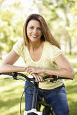Hispanic woman in park with bike — Stock Photo