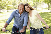 Couple riding bikes in park — Foto de Stock
