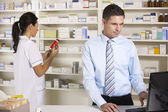 UK nurse and pharmacist working in pharmacy — Stockfoto