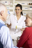 American pharmacist dispensing to senior couple — Stock Photo