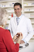 American pharmacist with senior woman in pharmacy — Stock Photo