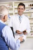 Farmacista americano con un uomo anziano in farmacia — Foto Stock