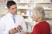 Farmacista americano con donna senior in farmacia — Foto Stock