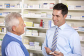 UK pharmacist serving senior man in pharmacy — Stock Photo