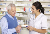 American pharmacist serving senior man in pharmacy — Foto Stock