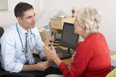 Britse gp praten met senior vrouw in de chirurgie — Stockfoto