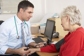 British doctor taking senior woman's blood pressure — Foto Stock