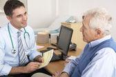 Gp de grande-bretagne parler à homme senior en chirurgie — Photo