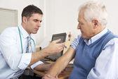 Britse gp injecteren senior man in de chirurgie — Stockfoto