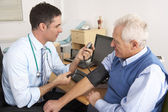 British doctor taking senior man's blood pressure — Foto de Stock