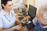 British nurse taking senior man's blood pressure — Stock Photo
