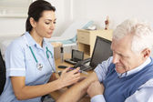 British nurse giving injection to senior man — Stock Photo