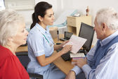 British nurse talking to senior couple — Stock Photo