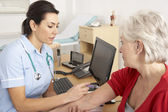 Britská zdravotní sestra dávat injekce na starší žena — Stock fotografie