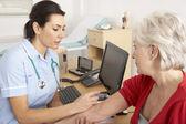 Enfermera británica dando inyección a mujer senior — Foto de Stock