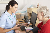 British nurse taking senior woman's blood pressure — Stock Photo