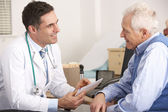 Médico americano falando com homem sênior na cirurgia — Foto Stock