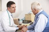 Amerykański lekarz mówi do starszy człowiek w chirurgii — Zdjęcie stockowe